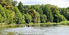 Ruhe und Entspannung auf dem Finowkanal in Brandenburg - dicht stehen die Bäume am Kanalufer. Ein Kanut fährt mit seinem Paddelboot kanalaufwärts.