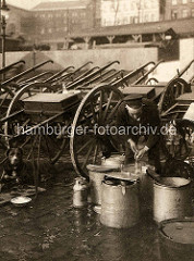 Abgestellte Milchkarren in Hamburg - ein Zughund liegt auf einer Matte; der Milchhändler reinigt Kannen und Flaschen.