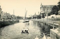 Historisches Bild vom Langen Kai in Brugge; Frachtschiffe liegen in der Gracht  -  rechts die Kirche der Heiligen Jungfrau Maria / Heilige Maagd Mariakerk, dahinter die Fassade vom Hospital Onze-Lieve-Vrouw-Ter-Potterie.