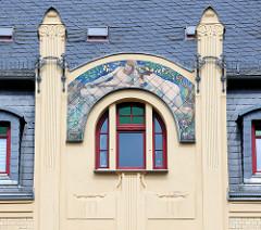 Denkmalgeschützte Fassade/Giebel eines Jugendstilgebäudes an der Wallstraße in Altenburg; bemalte Kacheln mit einem nackten Paar im Wald. Der Mann hat einen Fisch im Ketscher gefangen, die Frau trägt einen Blumenkranz im Haar.