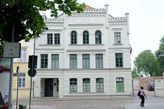 Wohnhaus, klassizistisches Wohngebäude mit Zinnengesims und figürlichen Schmuckdekor an der Hausfassade in der Hagenböcker Straße von Güstrow.