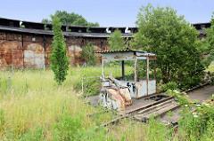 Stillgelegter, verwahrloster alter Lokschuppen an der Bahnstrecke in Güstrow - im Vordergrund die Auffahrt / Schienen zur Drehscheibe.