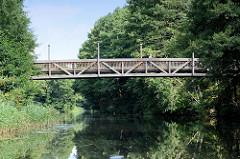 Holzbrücke / Fussgängerbrücke zwischen Bäumen über den Finowkanal.