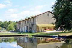 Messinghafen von Finow am Finowkanal, am Ufer ein Lagergebäude.
