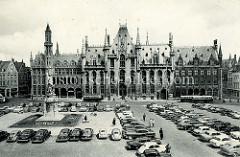 Alte Fotografie vom Grote Markt in Brügge; Autos parken auf dem Marktplatz, lks. das Denkmal für Jan Breydel und Pieter de Coninck, dahinter der um 1880 im Baustil der Neogotik errichtete  Provinciaal Hof, Regierungssitz der Provinz Westflandern.