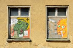 Vernagelte Fenster eines leer stehenden Gebäudes in Güstrow, die Holzplatten sind mit bunter Graffiti- Porträts versehen.