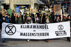 Trauermarsch der Graswurzelbewegung Extinction Rebellion XR in der Mönckebergstraße  in der Hansestadt Hamburg. Die DemonstrantInnen tragen Holzkreuze mit den Namen ausgestorbener Tier- und Pflanzenarten; Transparent Klimawandel - Massensterben.