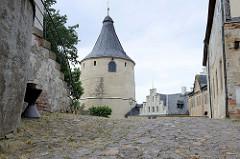 Kopfsteinpflaster, Blick zum Bergfried / Flasche im romanischen Baustil - Wehrturm im Schlossbereich von Altenburg - das Gebäude wurde auch als Wohnturm, Verlies, Kornspeicher oder zur Lagerung von Waffen genutzt.