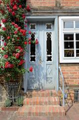 Historische Eingangstür eines Fachwerkgebäudes in der Altstadt von Güstrow, ein blühender Rosenstrauch mit roten Rosen wächst neben dem Eingang.