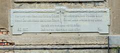Reliefinschrift eines 1907 errichteten Jugendstil - Wohnhauses in der Jahnstraße von Altenburg - Hier steht mein Haus, doch fällt's zu Staube, wenn's Gott nicht schützt :  das ist mein Glaube. Ich wohne drin, doch freudlos bliebe - Es mir, wohnt nich