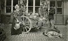 Qualitätskontrolle der Milch von mobilen Milchhändlern in Belgien; der Straßenverkauf der Milch findet aus großen Kannen statt, die auf einem zweirädrigen Karren stehen, der von Hunden gezogen wird.