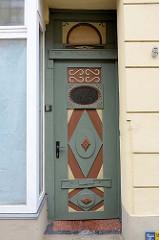 Alte  Eingangstür, Holztür in der Altstadt von Güstrow - farblich abgesetzte Zierverleistung sowie ein ovales Fenster mit Schnitzleisten als Türfüllung.