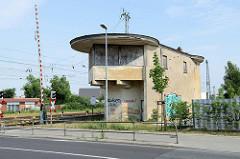 Leerstehendes Stellwerk mit vernagelten Fenstern an der Eisenbahnstraße in Güstrow; Architektur der 1960er Jahre mit rundem überstehendem Dach.