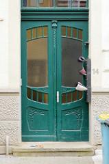 Alte Eingangstür im Stil des Historismus - geschwungene Formgebung des Türblatts un der Schnitzerei; Bilder der Architektur in Güstrow.