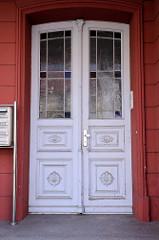 Alte Eingangstür im Stil des Historismus -   Zierverleistung und   farbiges Fensterglas; Bilder der restaurierten Altstadt von Güstrow.