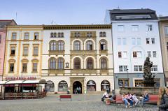 Historische Wohn- und Geschäftshäuser am Marktplatz von  Olmütz / Olomouc,  Jugendliche sitzen auf den Bänken am Herkulesbrunnen.