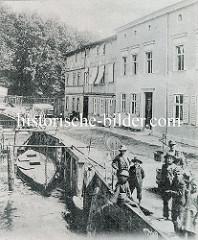 Historische Ansicht vom  Finowkanal bei Eberswalde; Fischer stehen am Ufer an dem Ketscher trocknen. Eine Waage mit einem Eimer zum Abwiegen von Fischen steht am Weg, im Hintergrund sitzt eine alte Frau auf einer Holzbank. Am Kai ist ein Holzbo