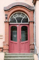 Alte Eingangstür im Stil des Historismus - Jugendstilform mit Schnitzerei und halbrundem Oberlicht; Bilder der Architektur in Güstrow.