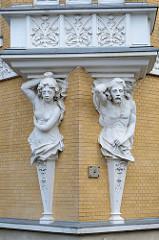 Eine männliche und weibliche Skulptur - Atlant und Karyatide - stützen einen Balkon eines denkmalgeschützten  Wohnhauses in der Straße Am Anger in Altenburg.