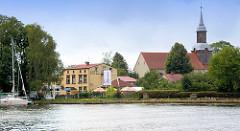 Fahrt von der Odermündung ins Stettiner Haff - Blick auf das Hotel und die Dorfkirche von Ziegenort /  Trzebież.