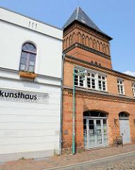 Ehemaliges, jetzt denkmalgeschütztes Hotelgebäude in der Baustraße von Güstrow, daneben das alte Feuerwehrgebäude - der gesamte Gebäudekomplex wird jetzt als Kinder-Jugend-Kunsthaus genutzt. Dahinter ist das  Dach des historischen Wasserturms zu erke