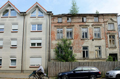 Alt + Neu; ein Neubau mit schlichter grauer Fassade und Spitzdach steht neben der Hausruine eines verlassenen Wohngebäudes dessen Putz ab blättert und die roten Mauersteine zum Vorschein bringt; das Gebäude ist mit einem Bretterzaun abgesperrt.
