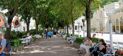 Promenade mit Ruhebänken unter Bäumen an der Kolonáda Maxima Gorkého / Maxim Gorki Kollonade  im Kurbad Marienbad / Mariánské Lázně.