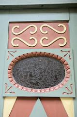 Eingangstür, Holztür in der Altstadt von Güstrow - farblich abgesetzte Zierverleistung sowie ein ovales Fenster mit Schnitzleisten als Türfüllung.