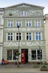 Wohnhaus / Geschäftshaus mit aufwändigem Stuckdekor auf der Hausfassade - Eingangstür mit figürlichem Schnitzwerk am Marktplatz in Güstrow.