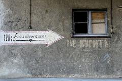Altes Speichergebäude mit Rauputzwand und zerbrochenen Fenster in Güstrow - handgemalter Pfeil mit Hinweis auf Löschwasser .