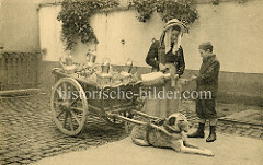 Milchverkäuferin in Belgien - Messingkannen mit Milch stehen im Stroh einer Karre, die von einem Hund gezogen wird. Die Milchfrau schenkt einem Jungen Milch in einen Becher ein.