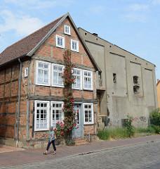 Denkmalgeschütztes Wohnhaus / Fachwerkhaus in der Hollstraße von Güstrow; daneben ein schlichtes Speichergebäude mit Rauputz.
