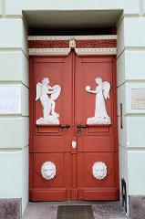 Klassizistische Eingangstür eines Geschäfts und Wohnhauses am Markt in Güstrow, allegorische Figuren stehen auf einem Sockel auf dem Türblatt der Doppeltür.