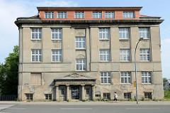 Leerstehendes Verwaltungsgebäude an der Eisenbahnstraße in Güstrow, von säulengestützter Tympanon am Eingang vom Reichsbahnamt - Reliefdekor Rad mit Flügeln / geflügeltes Eisenbahnrad.