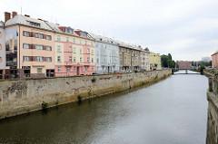 Mehrstöckige Wohnhäuser mit unterschiedlich farbigen Fassaden an der kanalisierten  Morava, March in Olomouc / Olmütz.