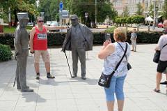 Ein Tourist lässt  sich an den Bronzestatuen / Figurengruppe von Kaiser Franz Josef I und Edward VII in Marienbad / Mariánské Lázně fotografieren.