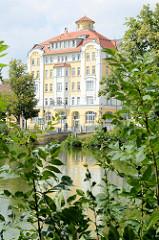 """Blick über den großen Teich zur aufwändig restaurierten, denkmalgeschützten ehemaligen Gaststätte Stadt Dessau. Das Gebäude wurde 1910 erbaut und in DDR-Zeiten von der sozialistische Handelsorganisation (HO) als Schnellimbiss """"Gastronom"""" betrieben. A"""