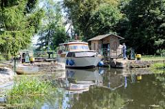 Die Schleusentore der Schleuse Ragöse am Finowkanal wurden vom Schleusenwärter von Hand geöffnet, ein Sportboot verlässt die Schleusenkammer.
