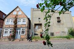 Denkmalgeschütztes Fachwerkhaus mit Rosenstock an der Fassade in der Hollstraße von Güstrow, daneben ein schlichtes graues Lagergebäude.