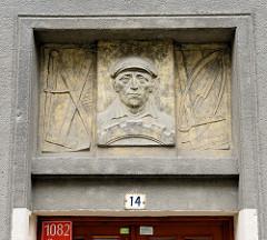 Steinrelief, Arbeiter-Porträt  mit Mütze über dem Eingang eines Wohnhauses in Olmütz / Olomouc.