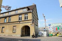 Leerstehendes Fachwerkgebäude mit Toreinfahrt und vernagelten Fenstern am Pferdemarkt in Güstrow, daneben eine Baustelle für geplante Neubauwohnungen.
