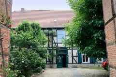 Historische Fachwerkarchitektur in Güstrow - blühende rote Rosen an der Hauswand vom Pfarrhaus.