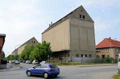 Hohe fensterlose Speichergebäude mit Satteldach und grauer Rauputzfassade mit Laderampe am Sankt Jürgens Weg in Güstrow.