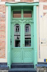 Alte Eingangstür im Stil des Historismus - aufgesetzte Zierverleistung und neoklassizistischen Türgriffen;  Bilder der restaurierten Altstadt von Güstrow.