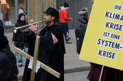 Trompeter auf dem Trauermarsch der Graswurzelbewegung Extinction Rebellion XR in der Mönckebergstraße Hamburgs. Plakat: Die Klimakrise ist eine Systemkrise.