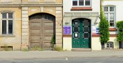 Alt und neu in der Eisenbahnstraße von Güstrow;  restauriertes Gebäude mit frisch lackierte Holztür und Glasfenstern neben einem verlassenen Gebäude dessen Toreinfahrt mit einem alten Tor verschlossen ist.