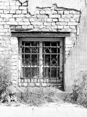 Schwarz-weiß Aufnahme vom Kellerfenster des ehemaligen Reichsbahnamtes in Güstrow, das Fenster ist mit einem Schmuckgitter versehen.