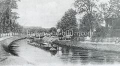 Historische Fotografie vom Finowkanal, ein Frachtkahn wird von einem Schlepper gezogen  - an Land stehen Kinder und blicken auf das Schiff.