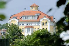 """Blick über den großen Teich zur aufwändig restaurierten, denkmalgeschützten ehemaligen Gaststätte Stadt Dessau. Das Gebäude wurde 1910 erbaut und in DDR-Zeiten von der sozialistische Handelsorganisation (HO) als  Schnellimbiss """"Gastronom"""" betrieben."""