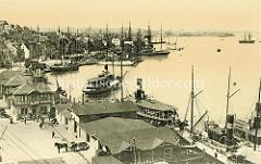 Alte Luftansicht vom Hafen in Flensburg - Frachtsegler liegen am Kai, dicht besetzte Fahrgastschiffe verlassenen den Anleger. An Land steht ein Pferdefuhrwerk und wartet auf Ladung.